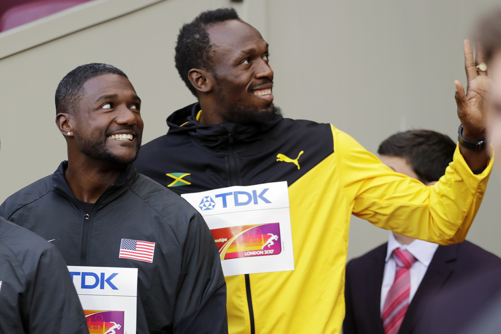 Justin Gatlin of the United States, gold, and Jamaica's Usain Bolt, bronze, from left, smile before the medal ceremony for the Men's 100m during the W...