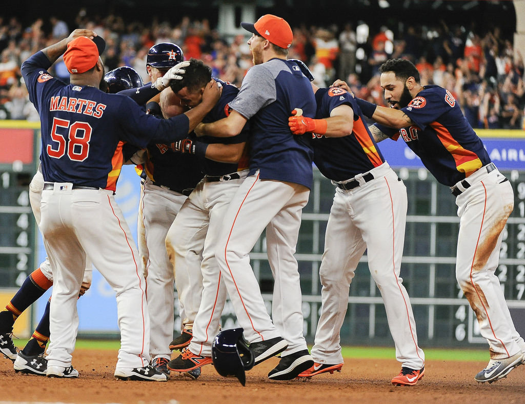Houston Astros' Juan Centeno, second from left, is mobbed by teammates after his walkoff RBI-single in a baseball game against the Toronto Blue Jays, ...