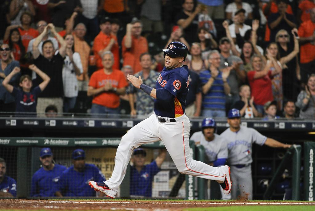 Houston Astros designated hitter Carlos Beltran runs home to score the game-tying run on Alex Bregman's two-run triple during the ninth inning of a ba...