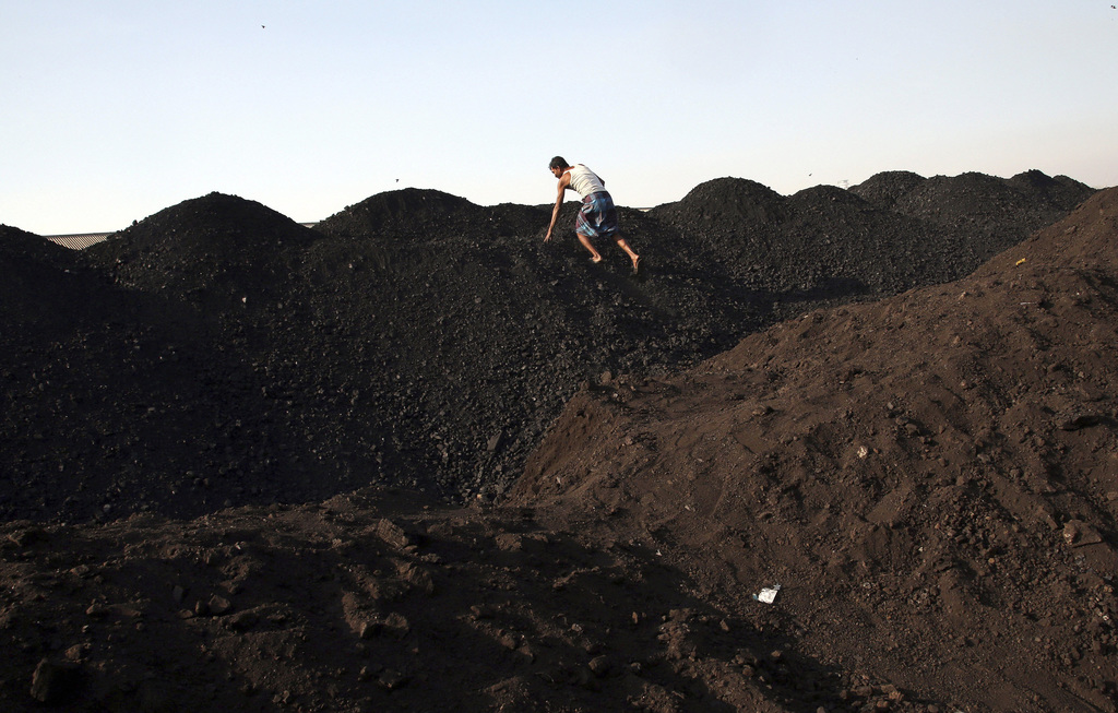 FILE - In this Jan. 7, 2015 file photo, an Indian man climbs a mound of coal at a coal yard in Mumbai, India. Within the wild energy market of the wor...