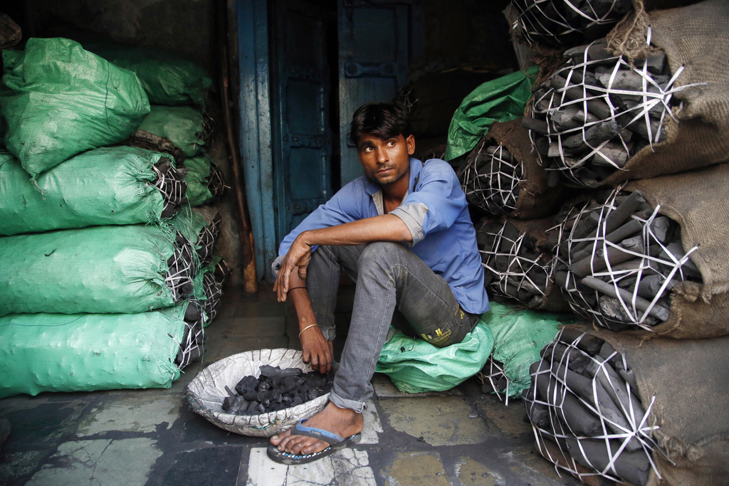 FILE- In this Dec. 3, 2015 file photo, a worker at a retail coal store awaits customers in Mumbai, India. India is the world's third-largest carbon em...