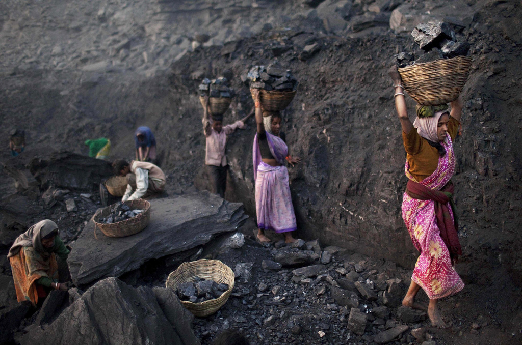In this Jan. 7, 2011, file photo, people carry baskets of coal scavenged illegally at an open-cast mine in the village of Bokapahari in the eastern In...