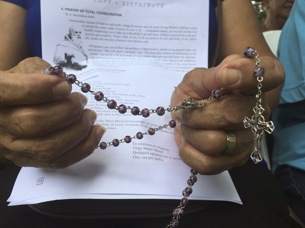 A woman holds rosary in her hand as people gather at Plaza de Espana, to pray for peace in Hagatna, Guam Sunday, Aug. 13, 2017.  Residents of the U.S.