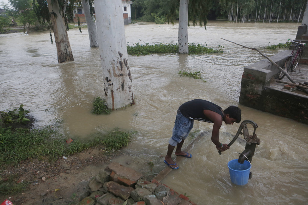 A Nepalese flood victim collects drinking water in Janakpur, Nepal, Sunday, Aug. 13, 2017. Landslides and flooding triggered by heavy rain have killed...
