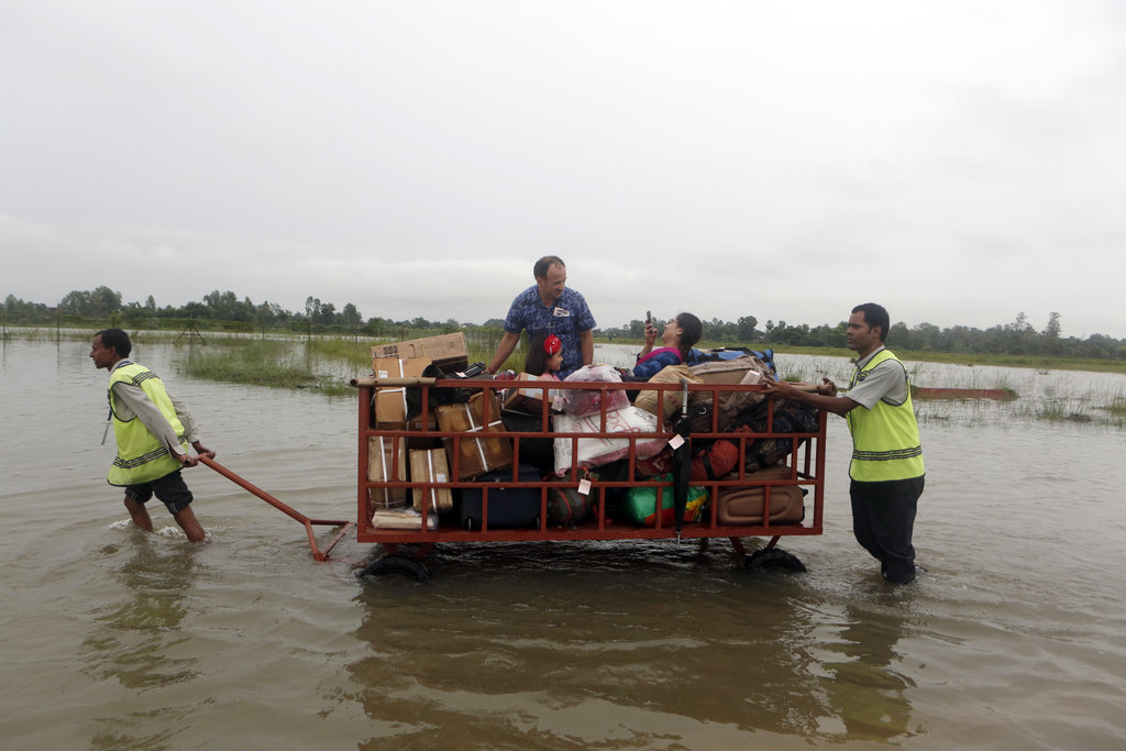 Passengers find their space in a luggage trolley as airport staff maneuver the same through the flooded Janakpur airport, Nepal, Sunday, Aug. 13, 2017...