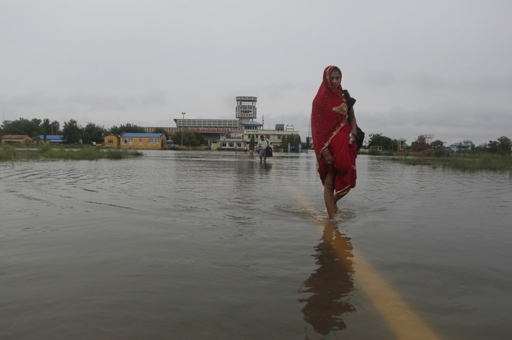 Passengers walk through the flooded Janakpur airport, Nepal, Sunday, Aug. 13, 2017. Landslides and flooding triggered by heavy rain have killed dozens...