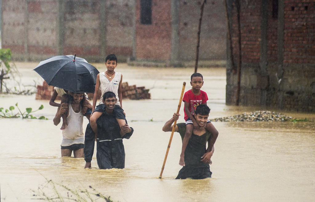 Nepalese men carry children on their shoulders as they wade through flood waters in village Ramgadhwa in Birgunj, Nepal, Sunday, Aug. 13, 2017. An off...