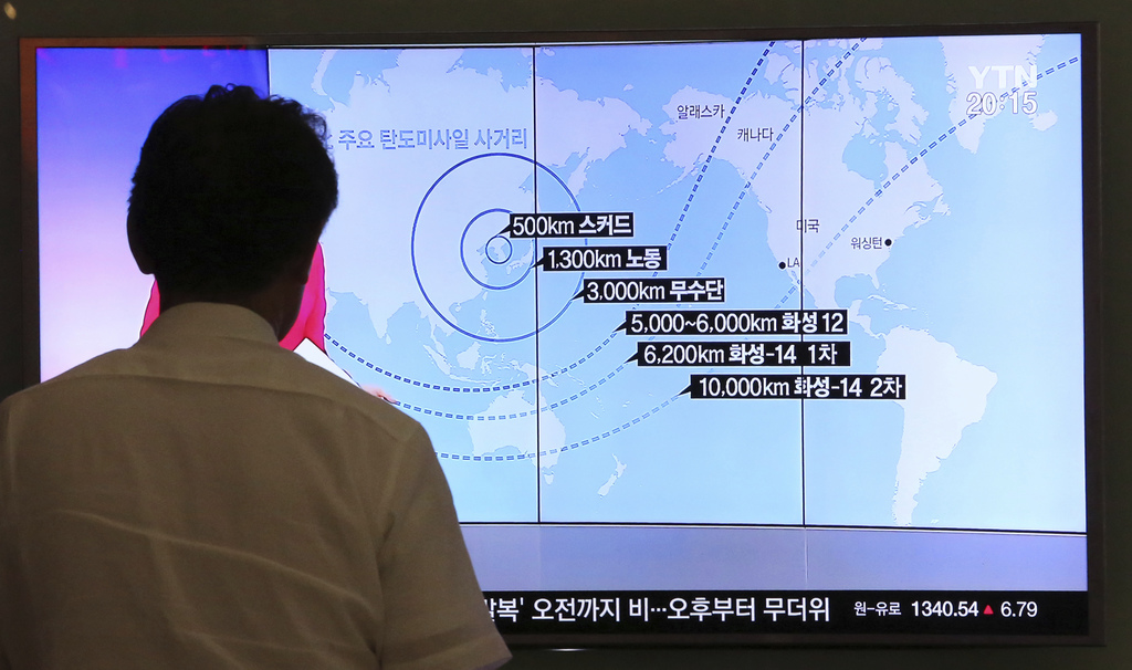 In this Aug. 10, 2017 photo, a man watches a TV screen showing a local news program reporting on North Korea's missiles, at the Seoul Railway Station ...
