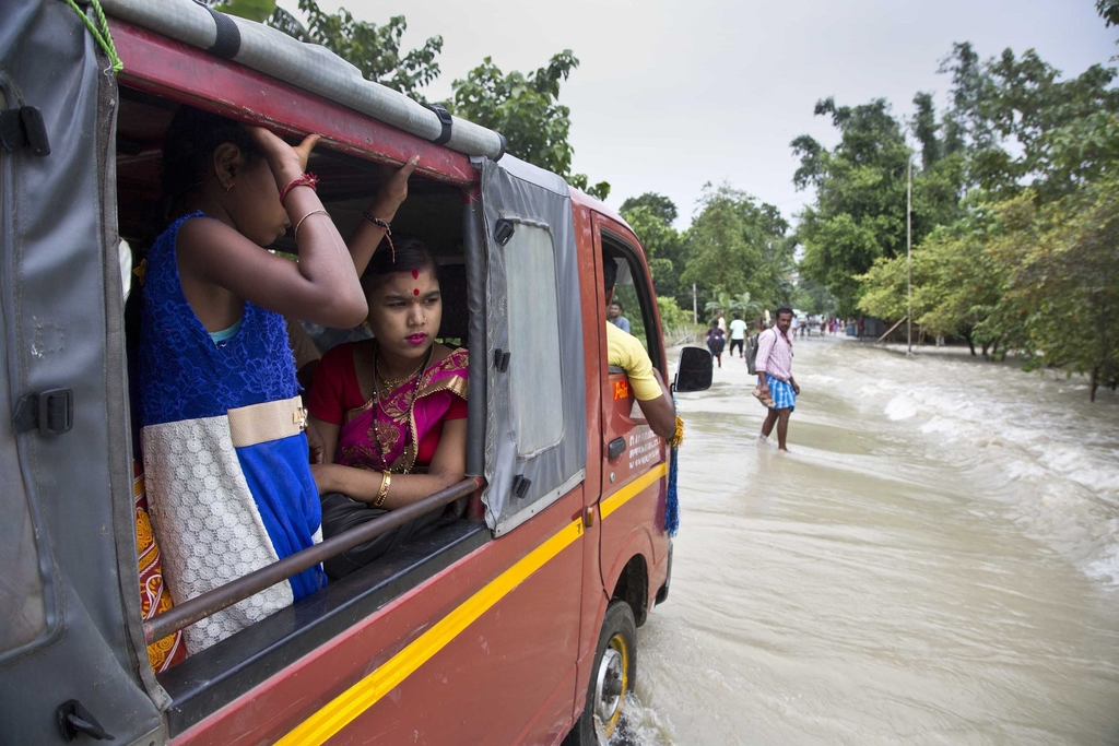 A vehicle drives through a flooded area in Murkata village east of Gauhati, India, Monday, Aug. 14, 2017. In the northeastern Indian state of Assam, t...