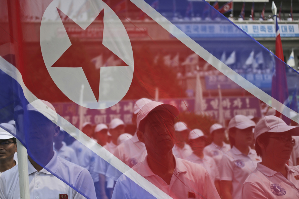 FILE - In this Aug. 15, 2015, file photo, participants stand behind a North Korean flag at a rally on Liberation Day, the anniversary of the end of Wo...