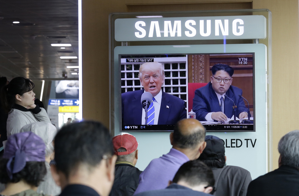 FILE - In the May 2, 2017 file photo, a TV screen shows images of U.S. President Donald Trump, left, and North Korean leader Kim Jong Un during a news...