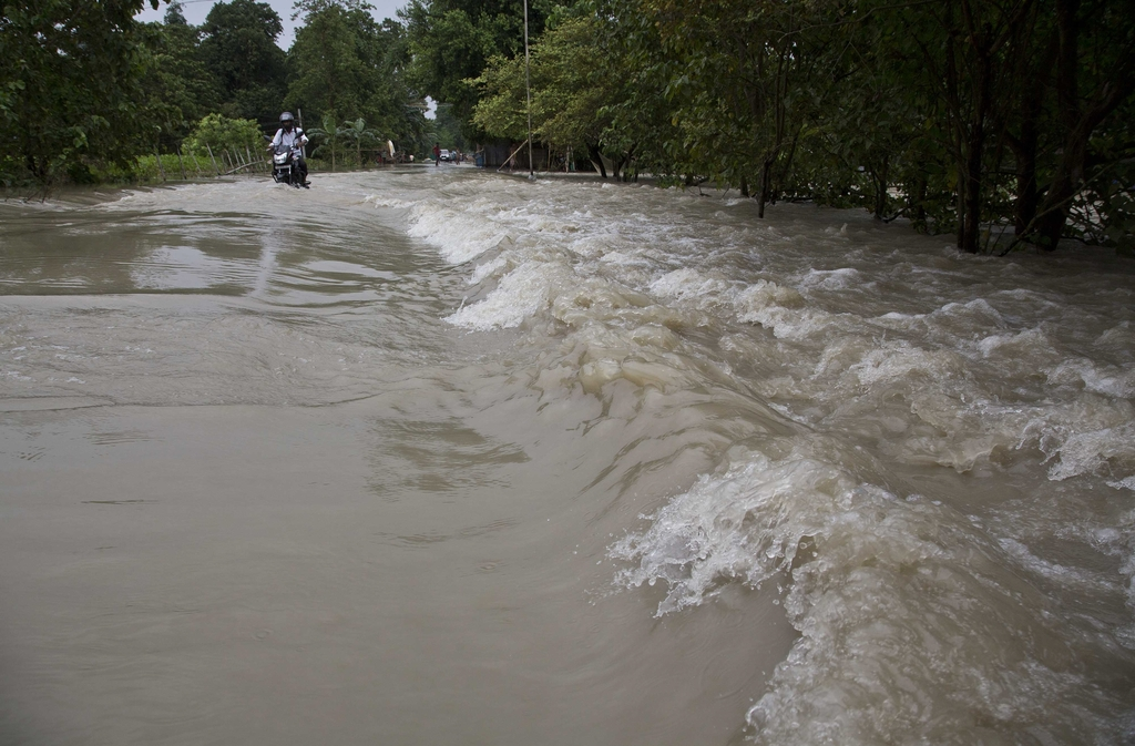 A motorbike drives through a flooded area in Murkata village east of Gauhati, India, Monday, Aug. 14, 2017. In the northeastern Indian state of Assam,...