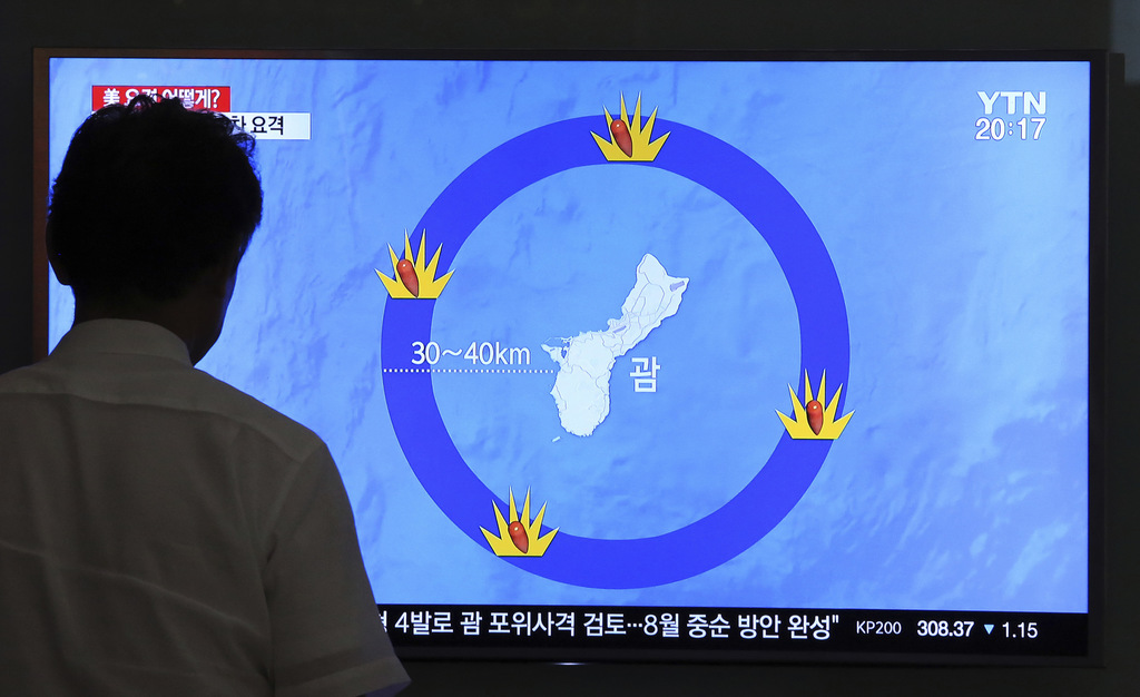 In this Aug. 10, 2017, file photo, a man watches a TV screen showing a local news program reporting on North Korea's threats to strike Guam with balli...