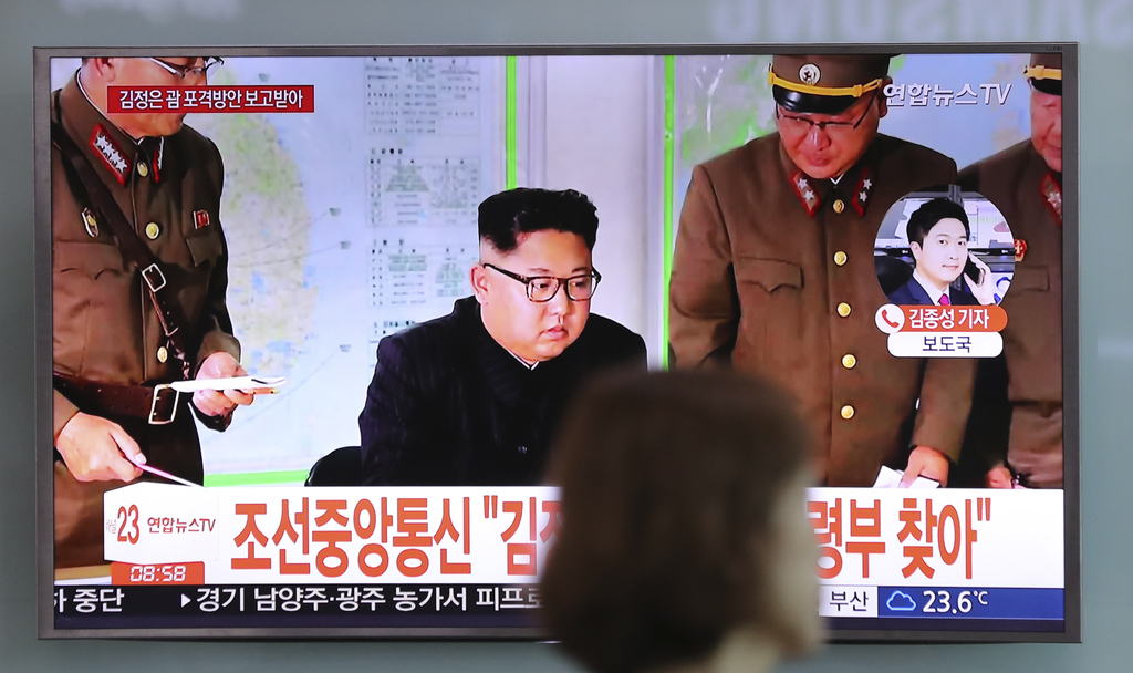 A woman walks by a TV screen showing a local news program reporting about North Korean military's plans to launch missiles into waters near Guam, with...
