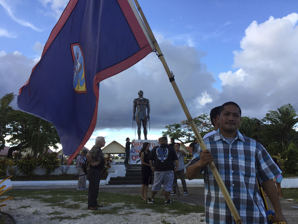 In this Aug, 14, 2017 photo, a man holds Guam flag during a peace rally in Hagatna, Guam. The threatened missile attack by North Korea on Guam has pro