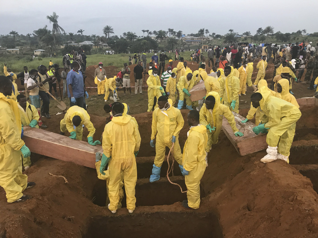 Volunteers handle a coffin during a mass funeral for victims of heavy flooding and mudslides in Regent at a cemetery in Freetown, Sierra Leone, Thursd...