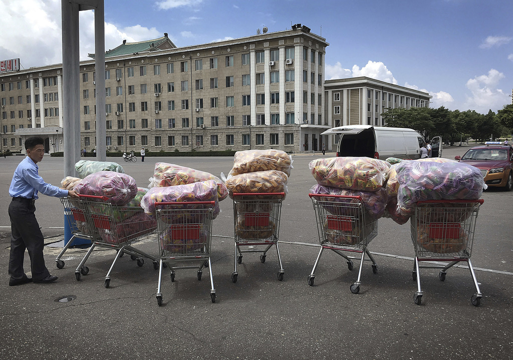 In this Saturday, June 25, 2016, file photo, a man waits with shopping carts at a parking lot in front of a department store in Pyongyang, North Korea...