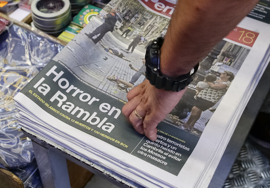 eaabacfa3765fd A man touches a newspaper displaying a photograph of the aftermath of the  terror attack in