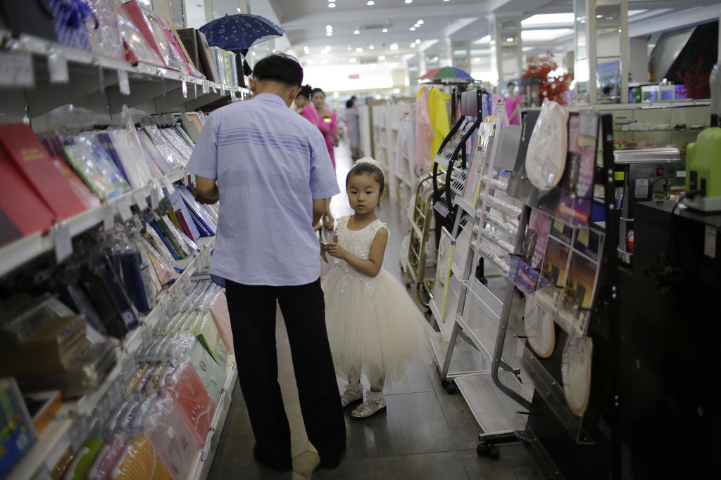 In this Monday, June 19, 2017, photo, a young girl and her father shop in the stationery department at the Potonggang department store in Pyongyang, N...
