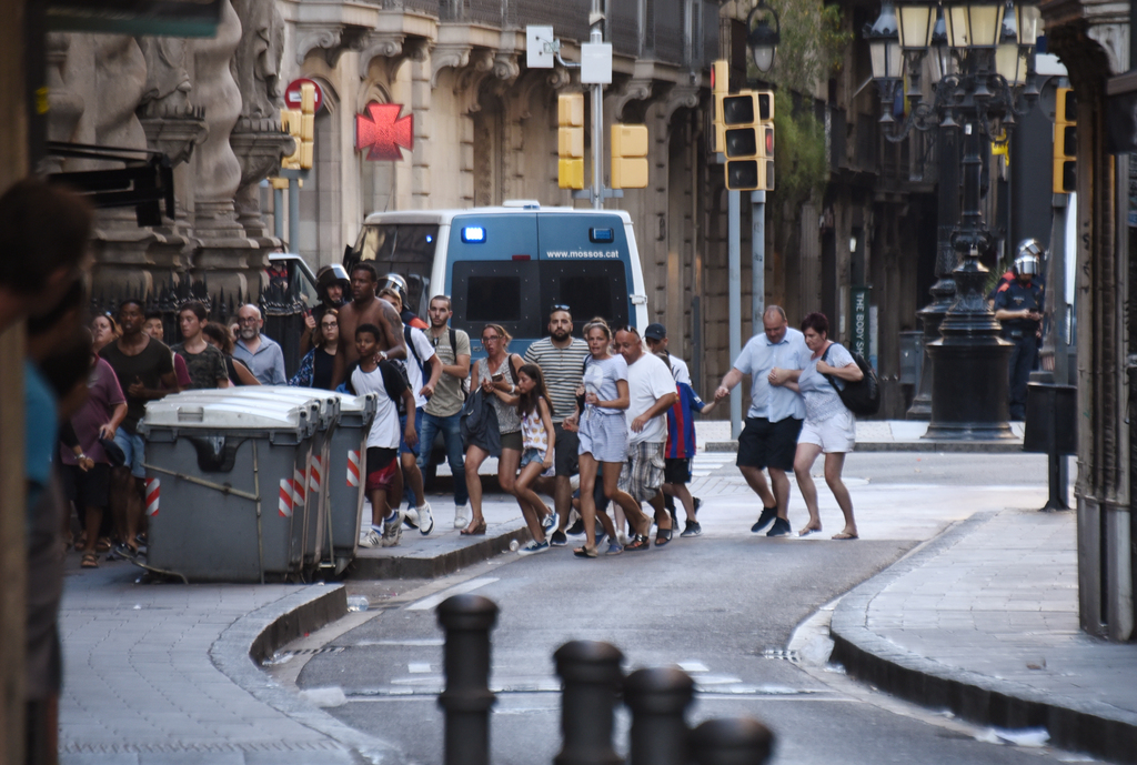 People flee from the scene after a white van jumped the sidewalk in the historic Las Ramblas district of Barcelona, Spain, crashing into a summer crow...