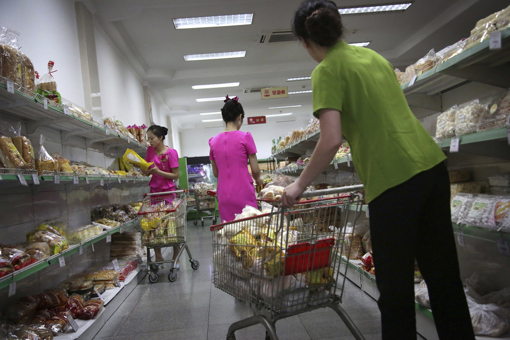 In this Monday, June 19, 2017, photo, staff at the Potonggang department store stock shelves with local and imported snacks, mostly from China, in Pyo...