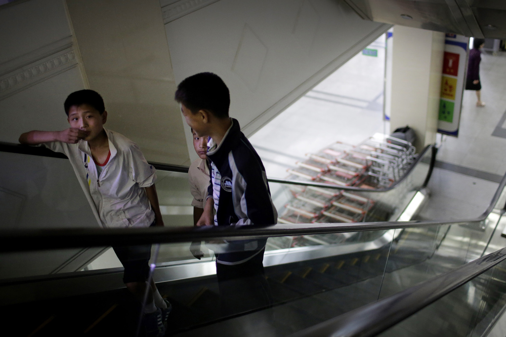 In this Monday, June 19, 2017, photo, boys ride an escalator which takes them to the household items and stationery section of the Potonggang departme...