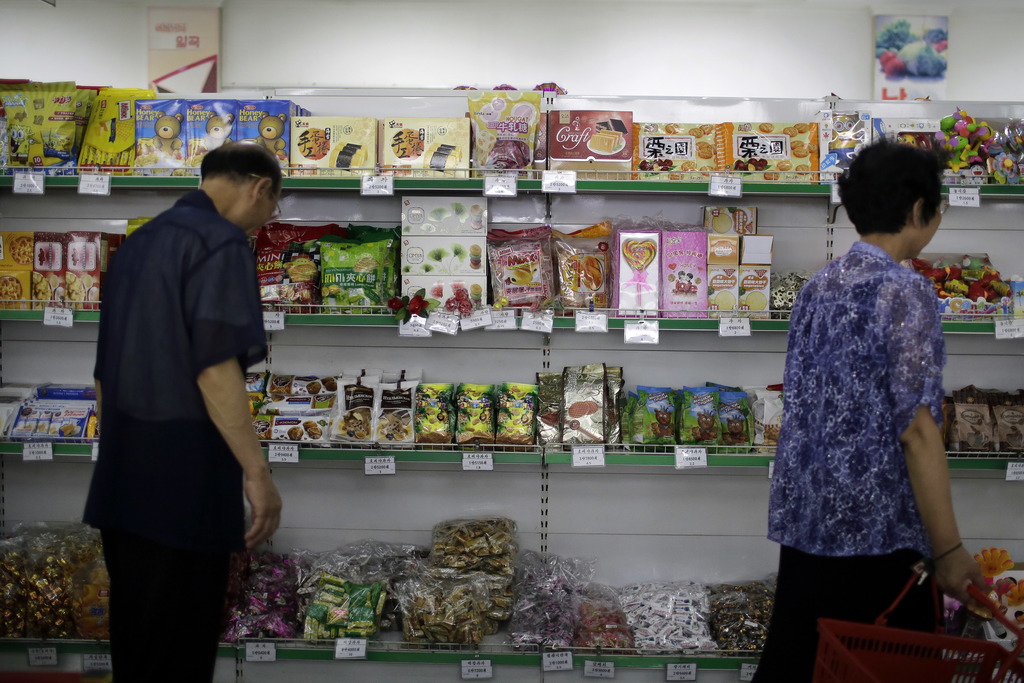 In this Monday, June 19, 2017, photo, people walk past a shelf displaying both local and imported snacks from China at the Potonggang department store...