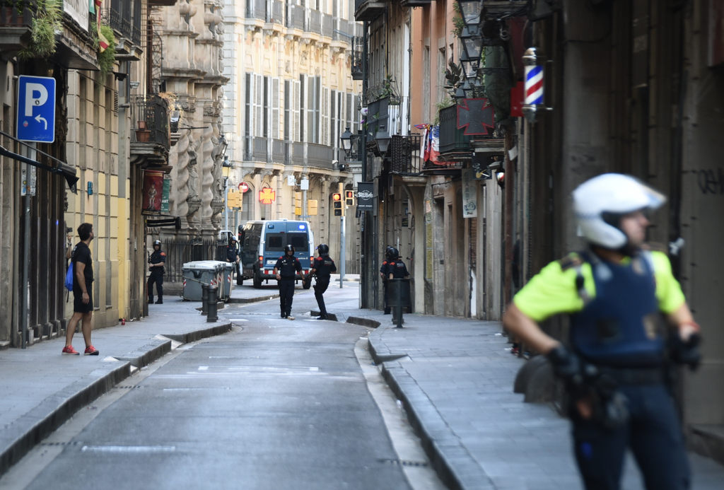 Police secure the area close to the scene after a white van jumped the sidewalk in the historic Las Ramblas district of Barcelona, Spain, crashing int...