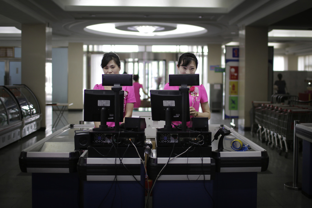 In this Monday, June 19, 2017, photo, cashiers stand at checkout counters waiting to serve customers at the Potonggang department store in Pyongyang, ...