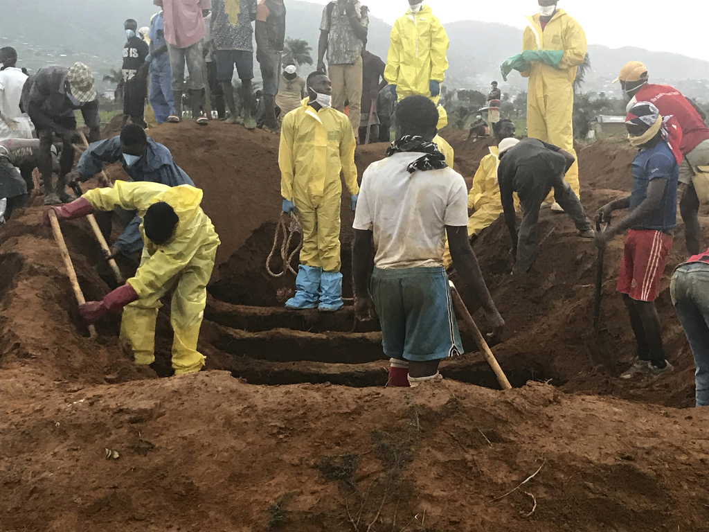 Volunteers prepare to bury coffins during a mass funeral for victims of heavy flooding and mudslides in Regent at a cemetery in Sierra Leone, Freetown...