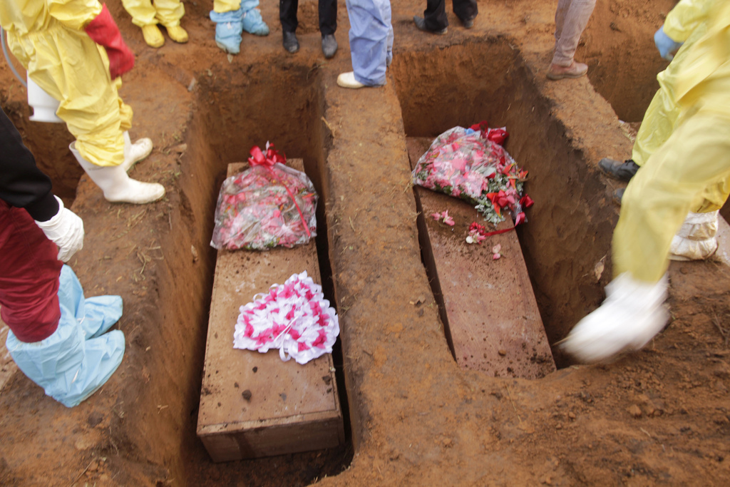 Volunteers bury coffins during a mass funeral for victims of heavy flooding and mudslides in Regent at a cemetery in Freetown, Sierra Leone, Thursday,...