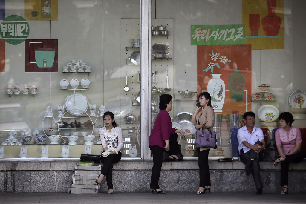In this Saturday, June 25, 2016, file photo, people sit in front of a window display of household items at a department store in Pyongyang, North Kore...