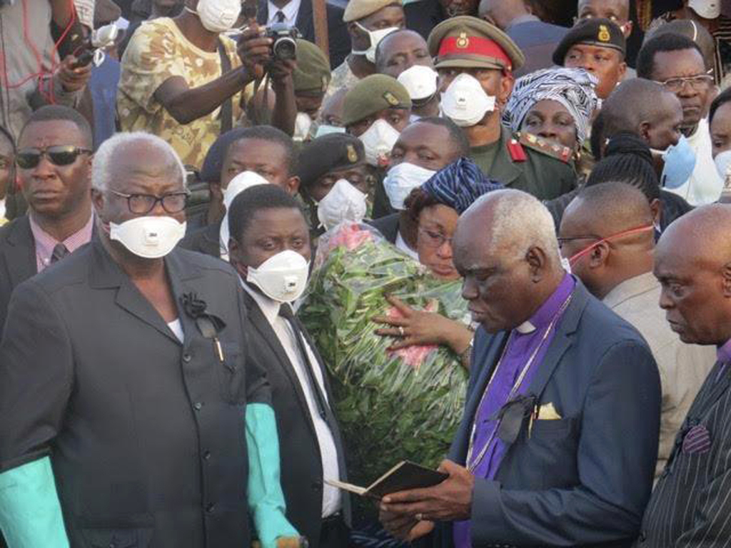 Sierra Leone President Ernest Bai Koroma, second from right, attends a mass funeral for victims of heavy flooding and mudslides in Regent at a cemeter...