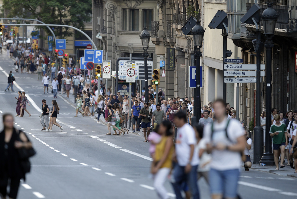 People walk down a main street in Barcelona, Spain, Thursday, Aug. 17, 2017. Police in Barcelona say a white van has mounted a sidewalk, struck severa...