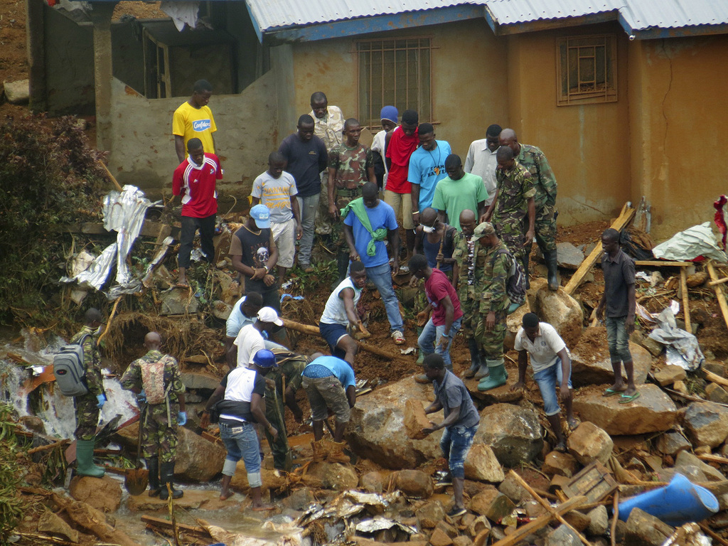 FILE- In this Tuesday, Aug.15, 2017 file photo, volunteers search for bodies from the scene of heavy flooding and mudslides in Regent, just outside of...
