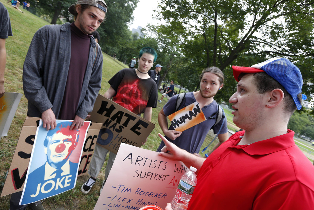 """Counterprotesters, rear, listen to a conservative activist, right, before a planned """"Free Speech"""" rally on Boston Common, Saturday, Aug. 19, 2017, in"""