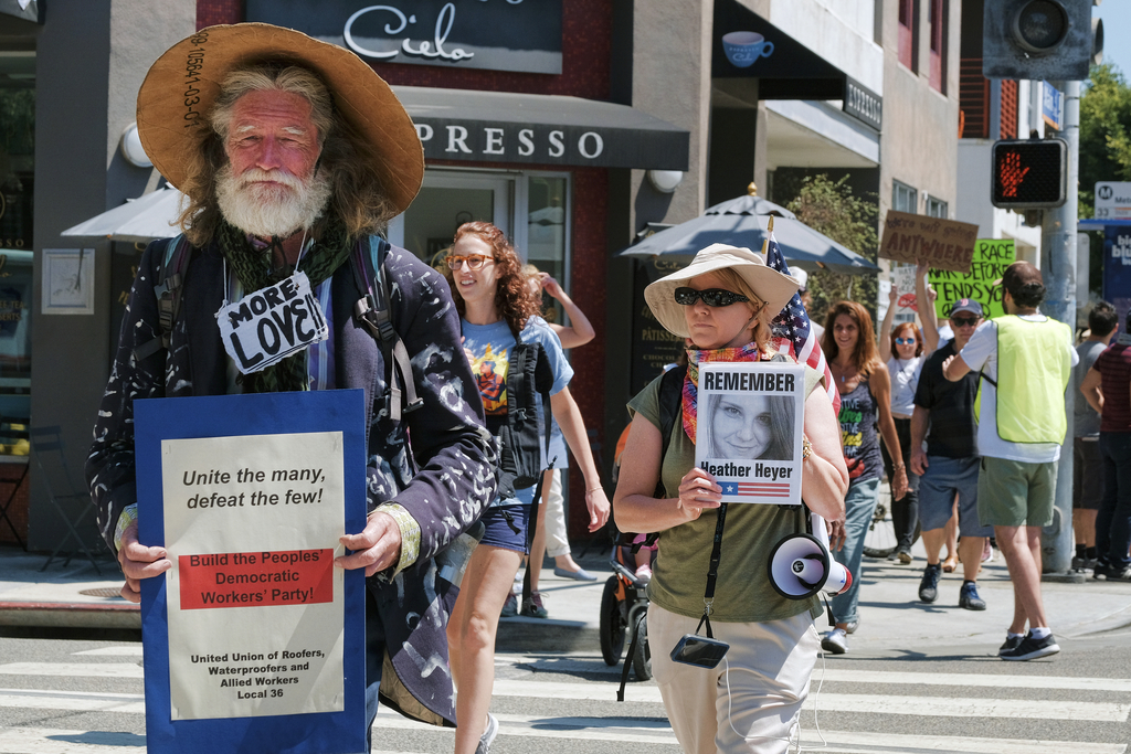 David Busch, left, a homeless community organizer is joined by Kris Tibor, carrying a photo in memory of Heather Heyer during protest walk in the Veni...