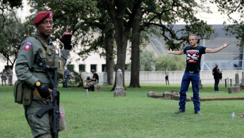 """Raymond Simmons, left, a veteran of the 82nd Airborne who served in Iraq and Afghanistan, gestures to Skylar Carson, right, during the """"Dallas Rally A"""