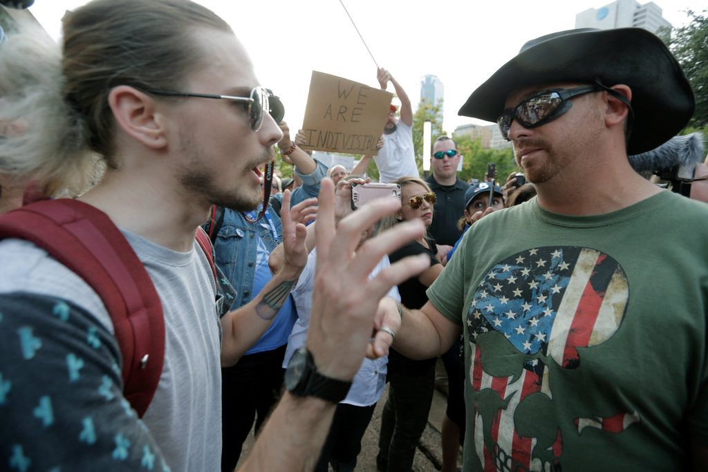 A demonstrator, left, with 'Dallas Rally Against White Supremacy' confronts a counter demonstrator Saturday, Aug. 19, 2017, in Dallas. (AP Photo/Brand
