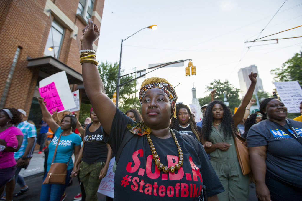 A protester raises her fist during a march that started in Centennial Olympic Park, Saturday, Aug. 19, 2017, in Atlanta. Protests took place across th
