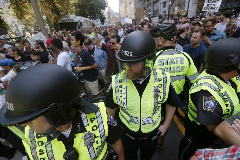 CORRECTS ACTIVITY OF POLICE TO PROVIDING EXIT LANE - State and local police stand amid counterprotesters to provide a lane for organizers to leave Bos...