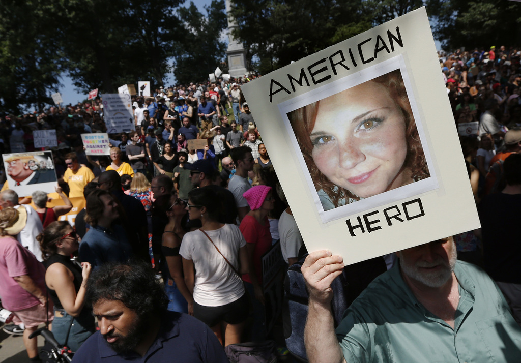 """A counterprotester holds a photo of Heather Heyer on Boston Common at a """"Free Speech"""" rally organized by conservative activists, Saturday, Aug. 19, 20"""