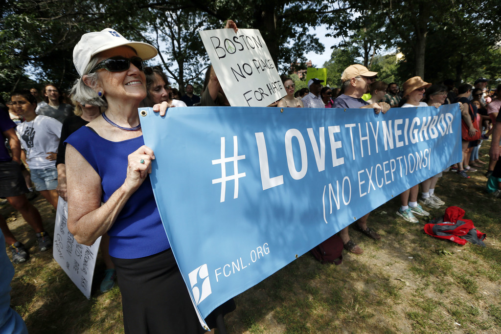 """Counterprotesters holds signs at a """"Free Speech"""" rally by conservative activists on Boston Common, Saturday, Aug. 19, 2017, in Boston. Thousands of co..."""