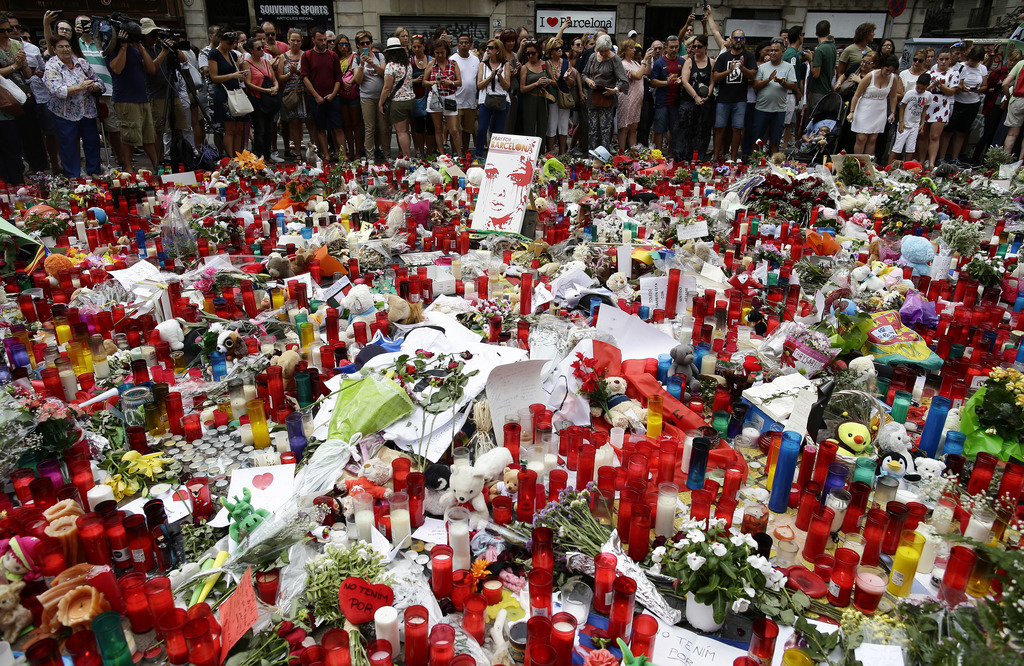 People stand next to candles and flowers placed on the ground after a terror attack that killed 14 people and wounded over 120 in Barcelona, Spain, Su...