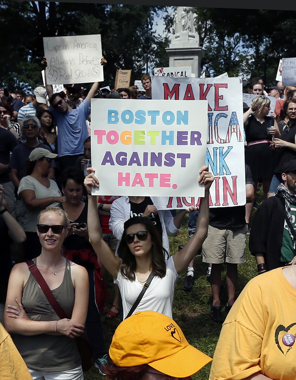"""Counterprotesters hold signs at a """"Free Speech"""" rally by conservative activists on Boston Common, Saturday, Aug. 19, 2017, in Boston.  Thousands of de"""