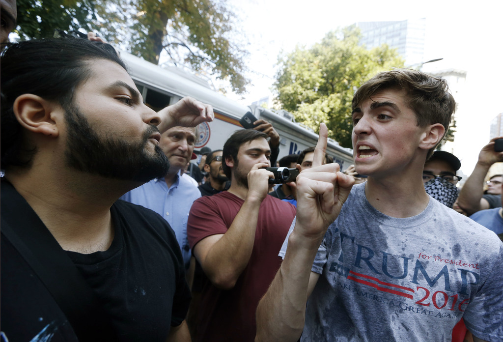 A man wearing a T-shirt bearing the name of President Donald Trump, right, argues with a counterprotester after being hit by a flying plastic bottle o
