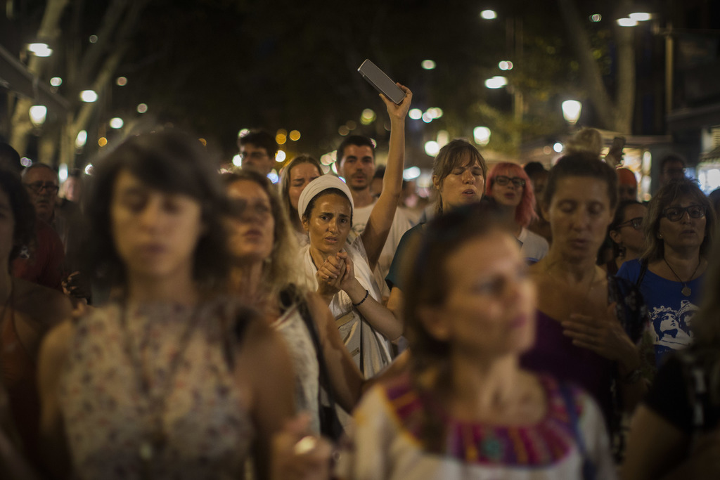 People sing as a protest against the van attack that took place 3 days ago, as they walk across the historic Las Ramblas promenade, Barcelona, Spain, ...