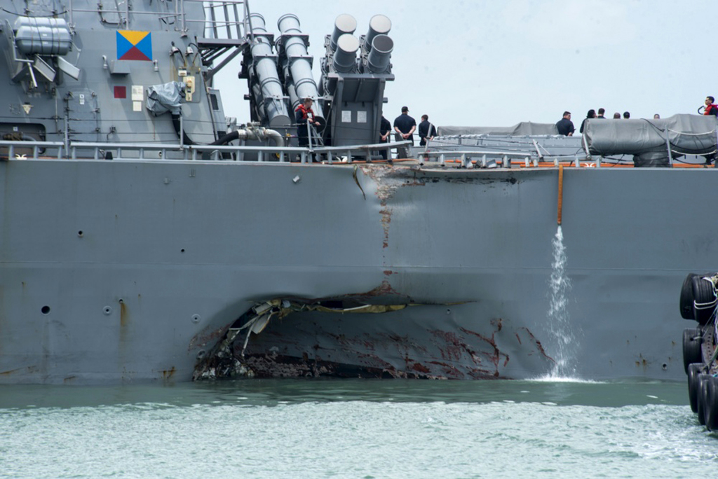 Damage to the portside is visible as the Guided-missile destroyer USS John S. McCain (DDG 56) steers towards Changi naval base in Singapore following ...