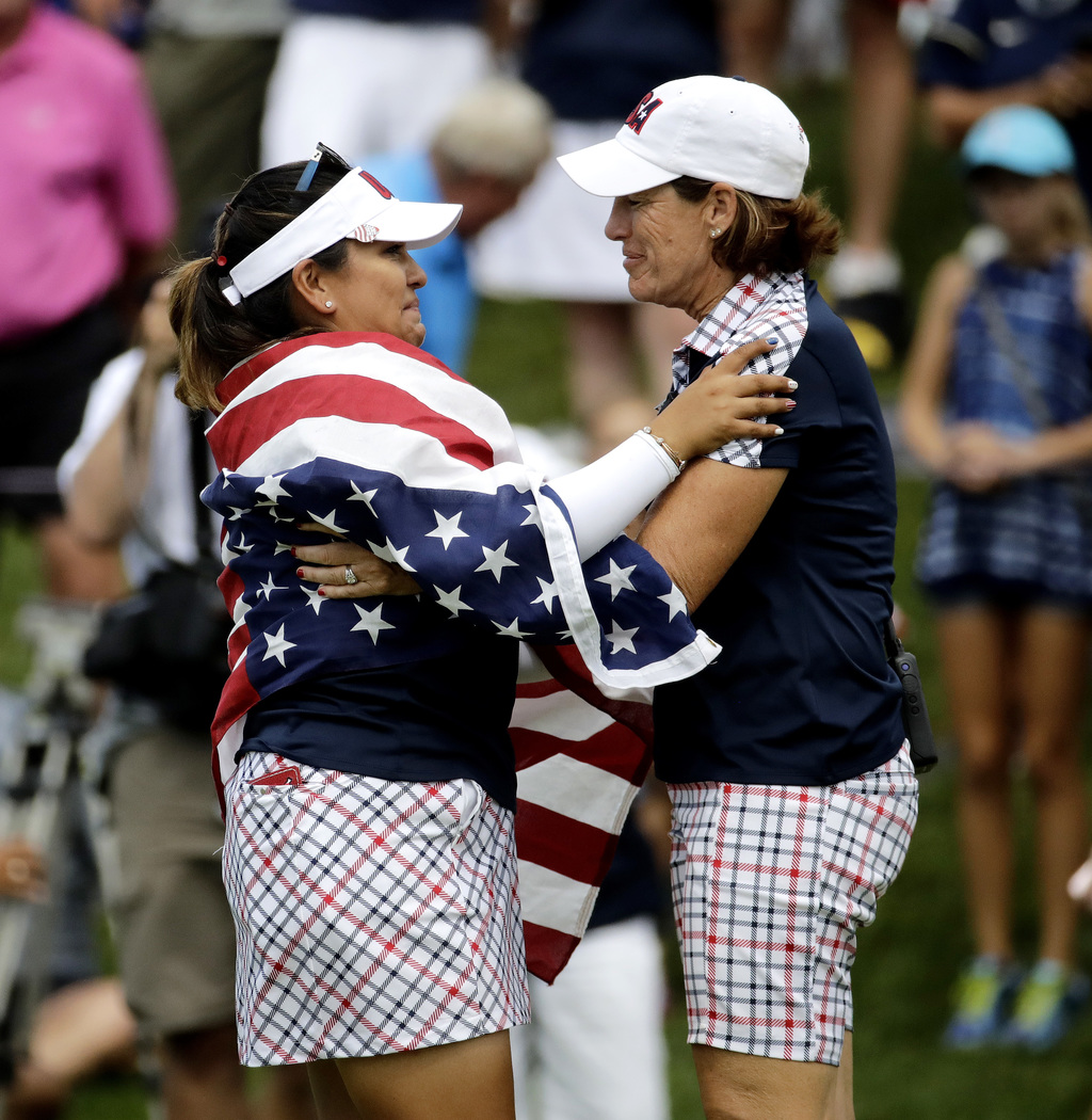 United States' Lizette Salas, left, celebrates with team captain Juli Inkster after clinching the winning half point during her singles match against ...