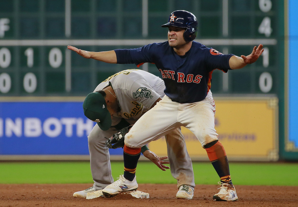 Houston Astros' Jose Altuve gestures as he safely steals second base ahead of the throw to Oakland Athletics shortstop Marcus Semien in the eighth inn...